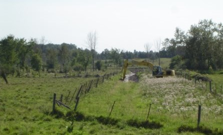 backhoe creating a ditch in a field